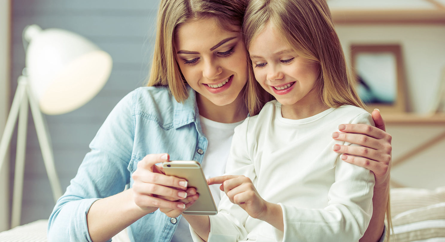 beautiful young mom and her little daughter are using an iPhone sitting on sofa at home